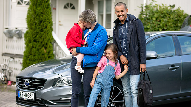 Familie står foran bil
