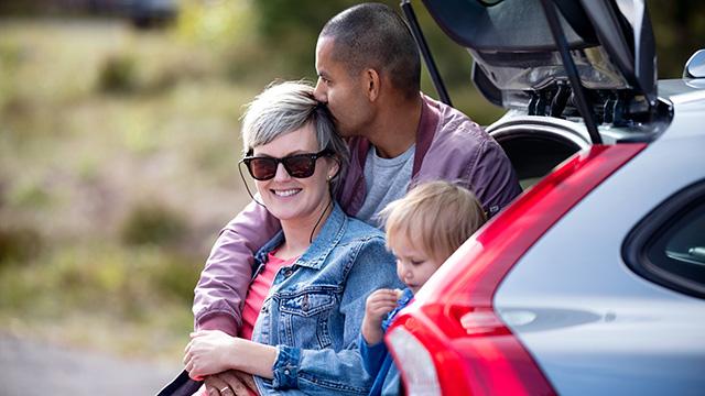 Familie sitter bak på bil