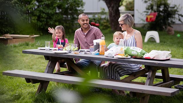 Familie spiser lunsj i parken