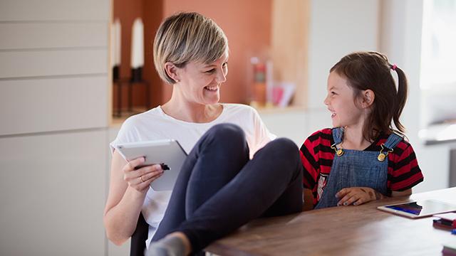 Mor og datter med iPad ved bordet