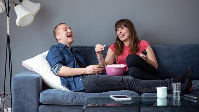 Par i sofa med popcorn