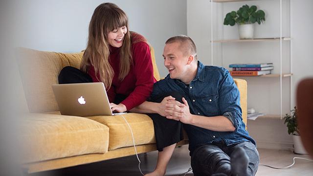 Par i sofa ser på PC
