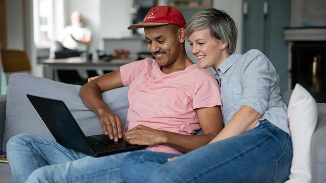 Par sitter sammen i sofa og ser på PC