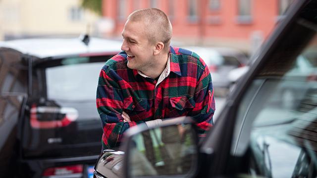 Smilende mann lener seg på bilen
