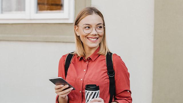 jente med mobil og kaffekopp