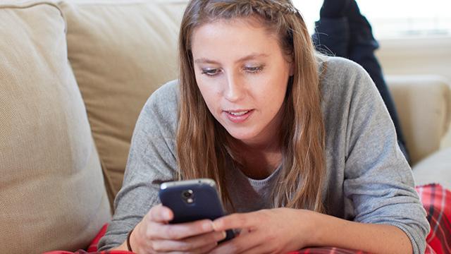 Jente i sofa med mobil