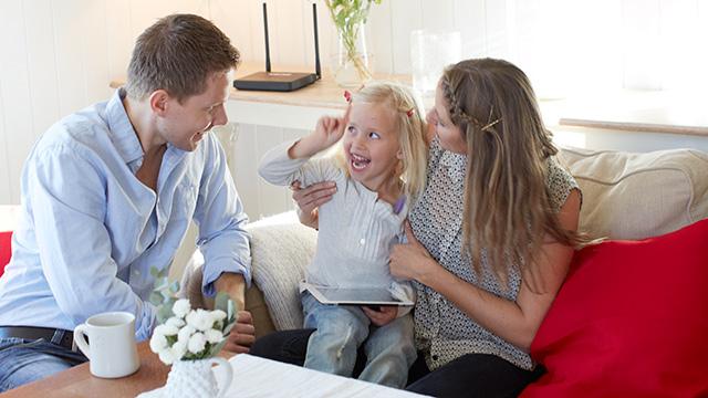 Far mor og datter tuller i sofaen